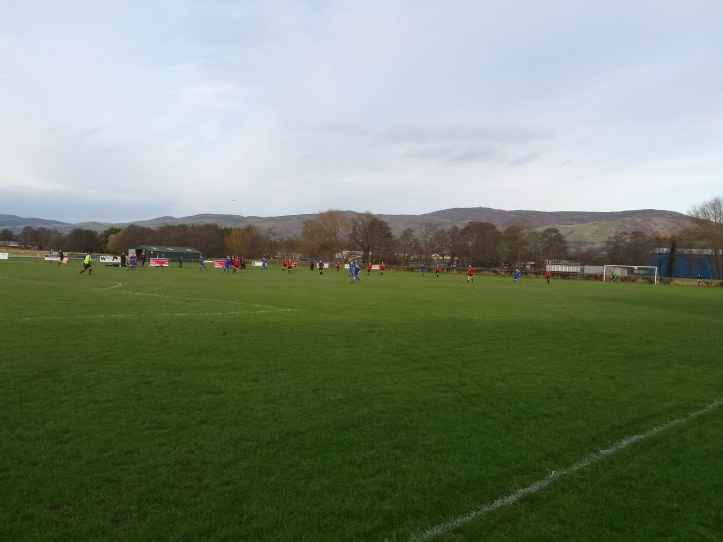 The teams playing with Moel Famau in the background