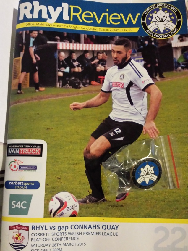 The programme for the match alongside the pin badge bought