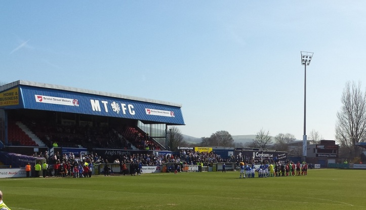 The teams line up in front of the Main Stand