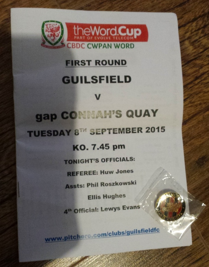 The programme for the match along with the pin badge bought