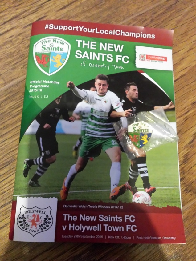The match programme and pin badge bought
